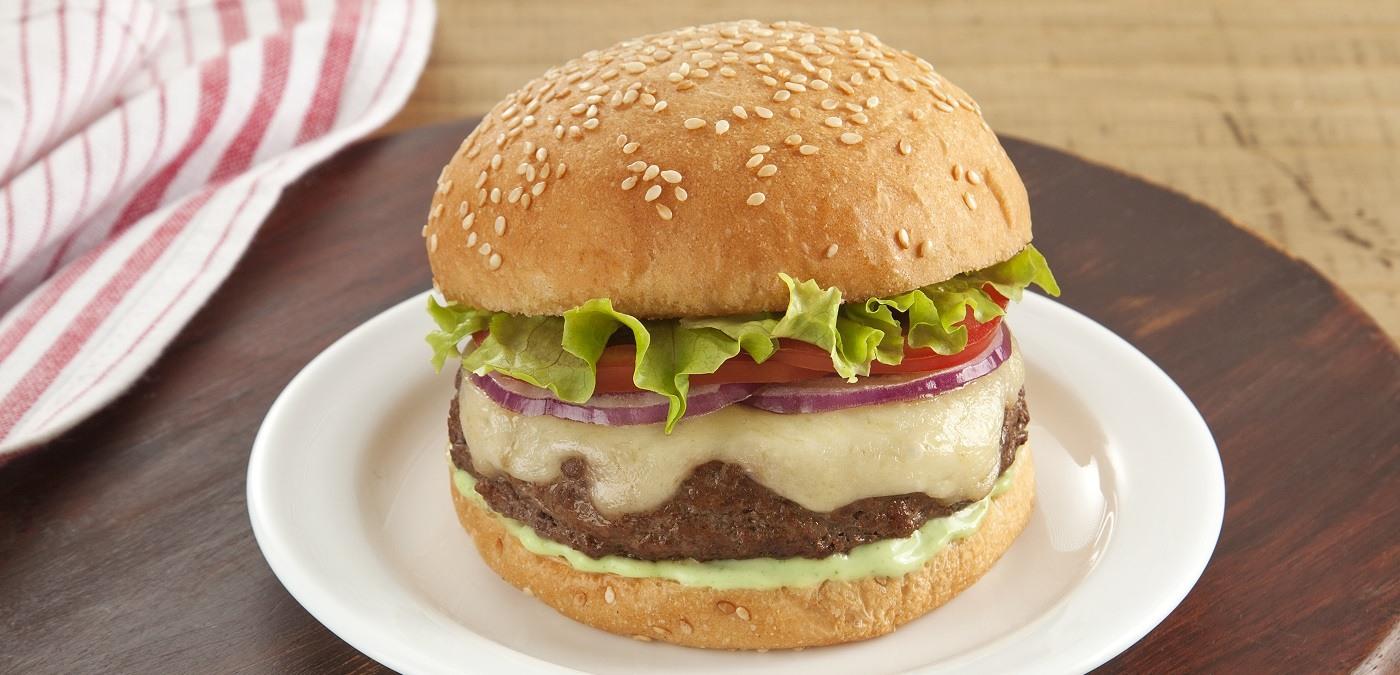 prato branco com um sanduiche de hamburguer, quejio e salada