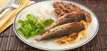 Prato com sardinhas assada, acompanhado com arroz, feijão e salada